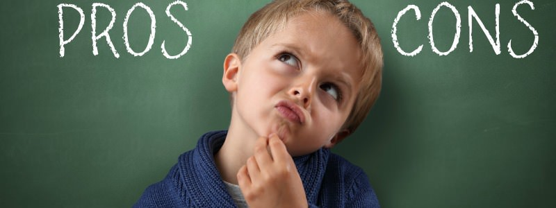 Child thinking with Pros and Cons on a blackboard